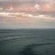 Isole Li Galli, Costiera Amalfitana, Penisola Sorrentina. Isolotti lontani in un mare scuro spazzato da raffiche di vento. Nel cielo nuvole colorate dagli ultimi raggi del sole.