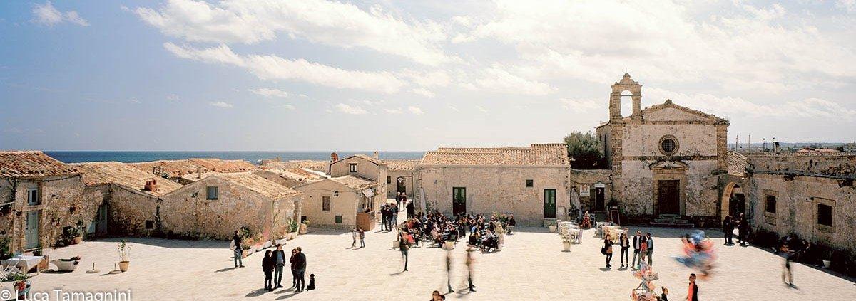 Marzamemi, 2018 - La piazzetta del borgo della tonnara, con la piccola chiesa e sullo sfondo il mare - Foto di Luca Tamagnini.
