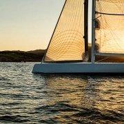 Nel mare della Costa Smeralda una barca a vela Wally al tramonto in controluce sullo sfondo la costa / Luca Tamagnini Catalogo 2009-020