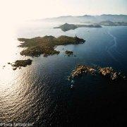 Sardegna, Il mare in controluce e l'Isola dei Cavoli con sullo sfondo Capo Carbonara (foto aerea)