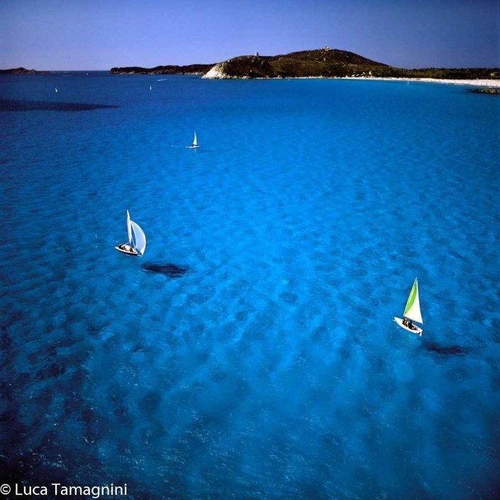Villasimius-Piccole-barche-a-vela-(derive)-navigano-nel-mare-turchese-della-rada-di-Porto-Giunco
