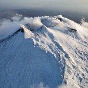 Etna cratere innevato da alta quota sullo sfondo il mare del Golfo di Catania