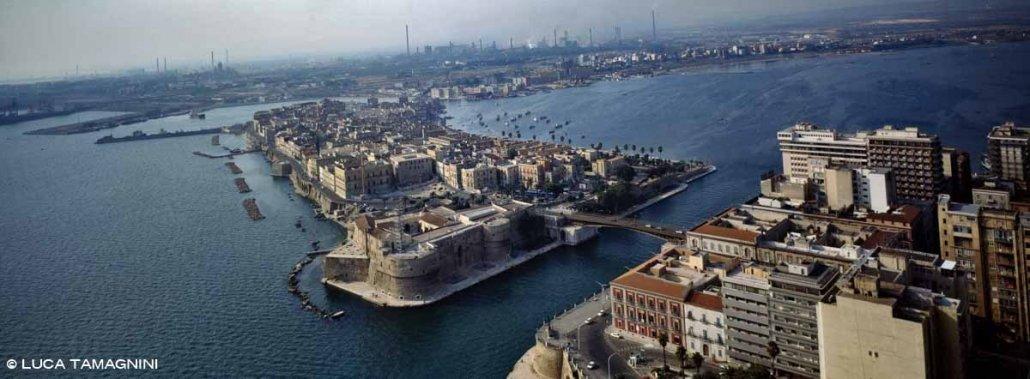 Taranto Città Vecchia Isola Borgo Antico dal cielo sullo sfondo l'area industriale con le ciminiere del centro siderurgico
