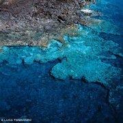 Foto Mare Sicilia. Isola di Linosa trasparenze del mare tra gli scogli di pietra lavica dal cielo