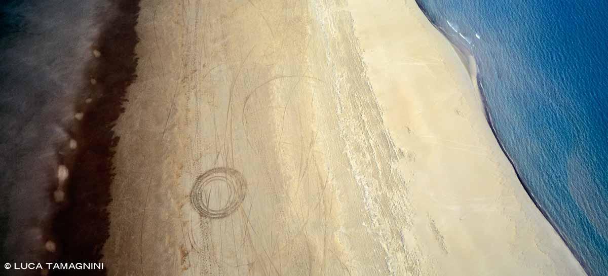 Villasimius, Spiaggia Timi Ama, Stagno di Notteri, segni nella sabbia e mare di Porto Giunco dal cielo (foto aerea)