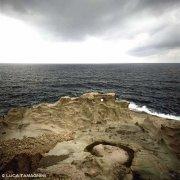 Sardegna, scogliera di rocce di tufo nei pressi della costa di Torre Argentina (Capo Marargiu) sullo sfondo il mare / Luca Tamagnini Catalogo 1992-007