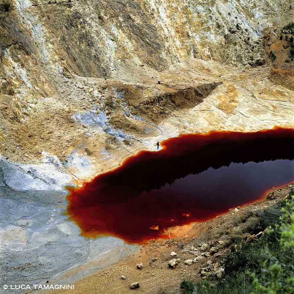 Foto Isola d'Elba. Laghetto delle Conche Miniere di Rio Albano l'acqua del laghetto è di colore rosso sangue a causa dell'ossidazione del ferro contenuto nei sedimenti di scavo