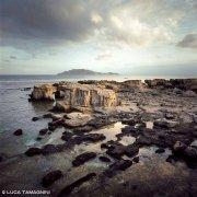 Foto Mare Sicilia. Isola di Favignana antiche cave di tufo sul mare sullo sfondo l'Isola di Levanzo