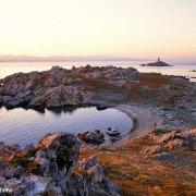 Arcipelago di La Maddalena, Isola di Corcelli piccola spiaggia con gommone sullo sfondo il faro di Barettinelli di Fuori / Luca Tamagnini Catalogo 2005-040