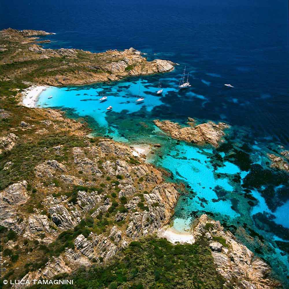 Costa Smeralda, Isola di Mortorio dal cielo con la spiaggia e le barche in rada / Luca Tamagnini Catalogo 2005-043