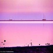 Sardegna, Villasimius Stagno di Notteri al tramonto con due barche a vela nella rada di Porto Giunco