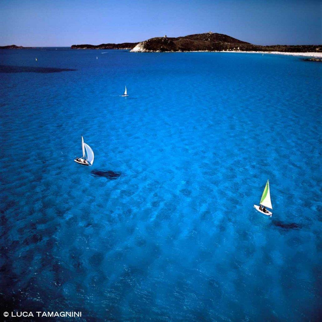 Sardegna, Villasimius Rada di Porto Giunco dal cielo con piccole barche a vela (laser) in un mare turchese (foto aerea)