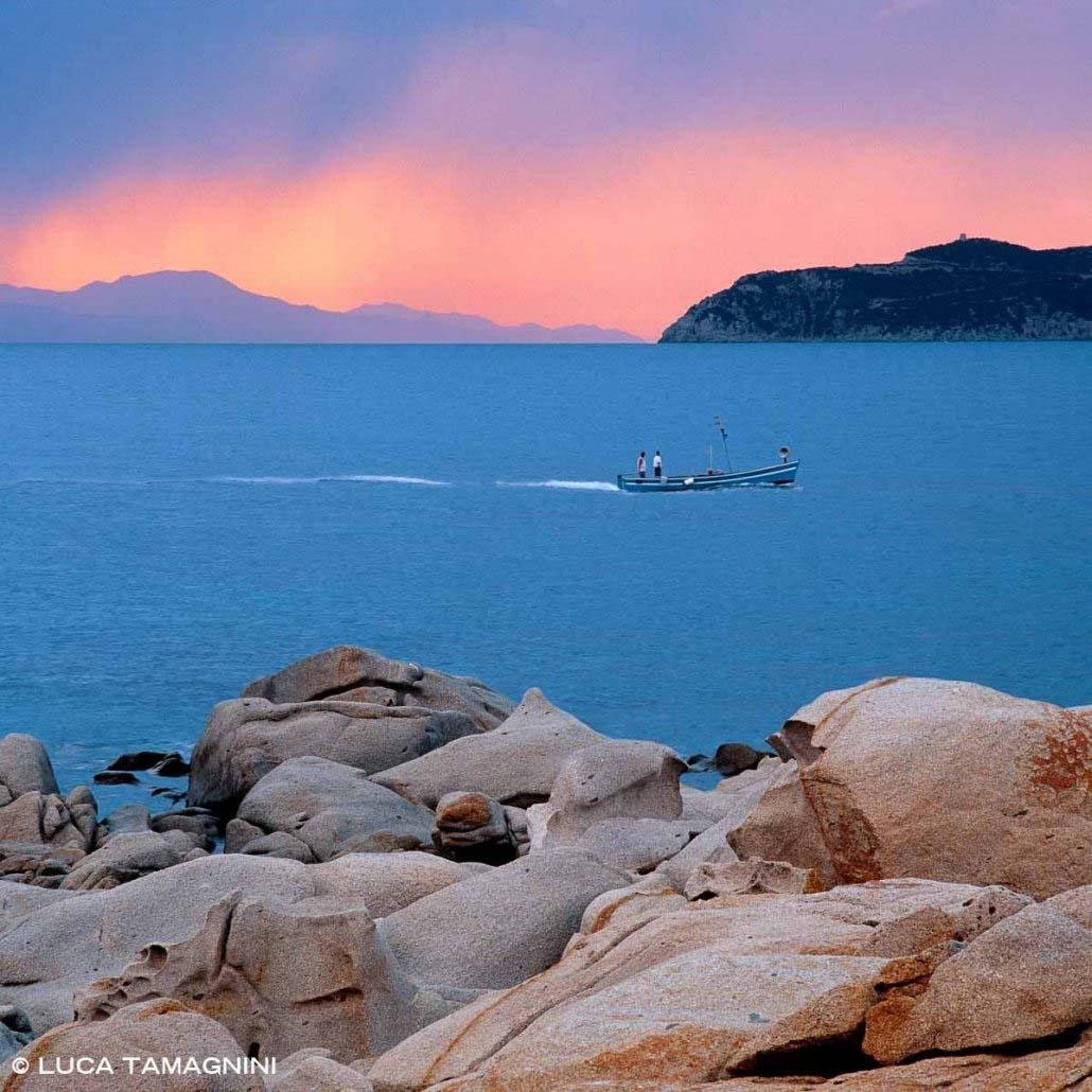 Capo Cargonara sud Sardegna Villasimius Punta Santo Stefano barca di pescatori in mare in cielo rosa del tramonto (Foto Mare Sardegna / Catalogo Luca Tamagnini)