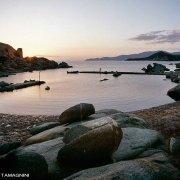 Sardegna, Isola dei Cavoli, approdo del faro al tramonto con una figura di donna lontana sul molto