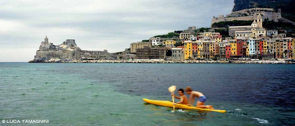 Foto Mare Liguria. Portovenere, borgo e Chiesa di San Pietro con in mare una canoa con a bordo due bambini