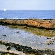 Siracusa Plemmirio antiche cave sul mare a Punta della Mola sullo sfondo una barca a vela.