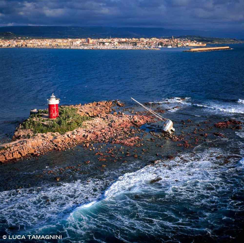 Sardegna, Alghero Isola della Maddalenetta dal cielo con un relitto di barca a vela e il fanale (foto aerea) / Luca Tamagnini Catalogo 2008-038