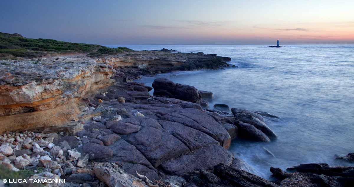 Sardegna, Isola di Sant'Antioco, la costa nei pressi dello Scoglio Mangiabarche con il faro in una luce crepuscolare / Luca Tamagnini Catalogo 2009-030