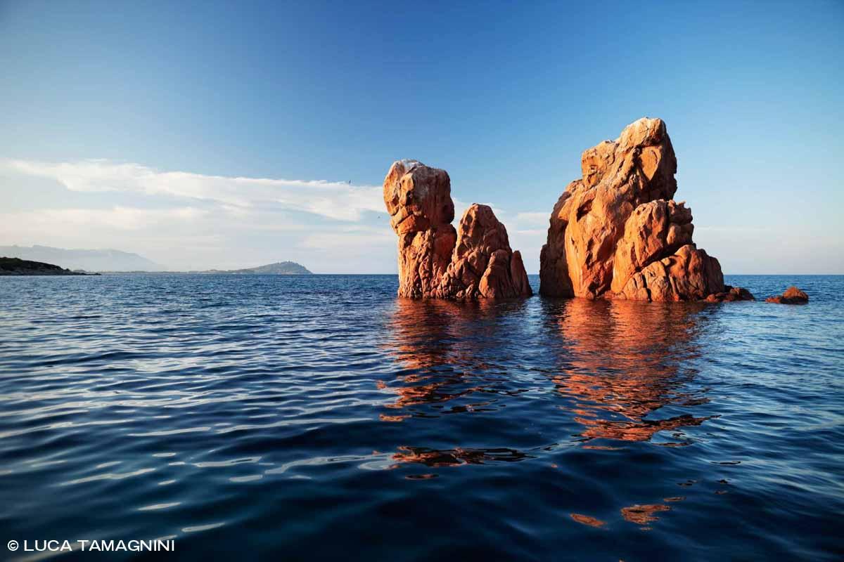 Sardegna, Faraglioni di Cea di granito rossastro circondati da un mare blu scuro