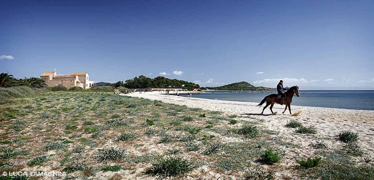 Sardegna, Spiaggia di Nora con cavallo e cavaliere sullo sfondo la Chiesetta di Sant'Efisio / Luca Tamagnini Catalogo 2010-039
