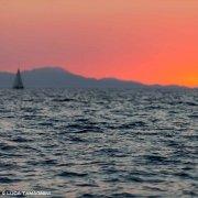 Golfo di Cagliari, mare in primo piano, sullo sfondo una barca a vela sfocata con la costa e un cielo colorato dal tramonto