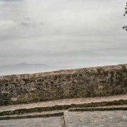 Castiglione della Pescaia mura della Fortezza Medioevale sullo sfondo il mare e lontano sull'orizzonte il Monte Argentario