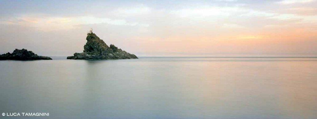 Palmi Scoglio Olivella in un mare piatto al tramonto