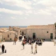 Marzamemi piazzetta del borgo della tonnara con gente e facciata della chiesa dei tonnaroti