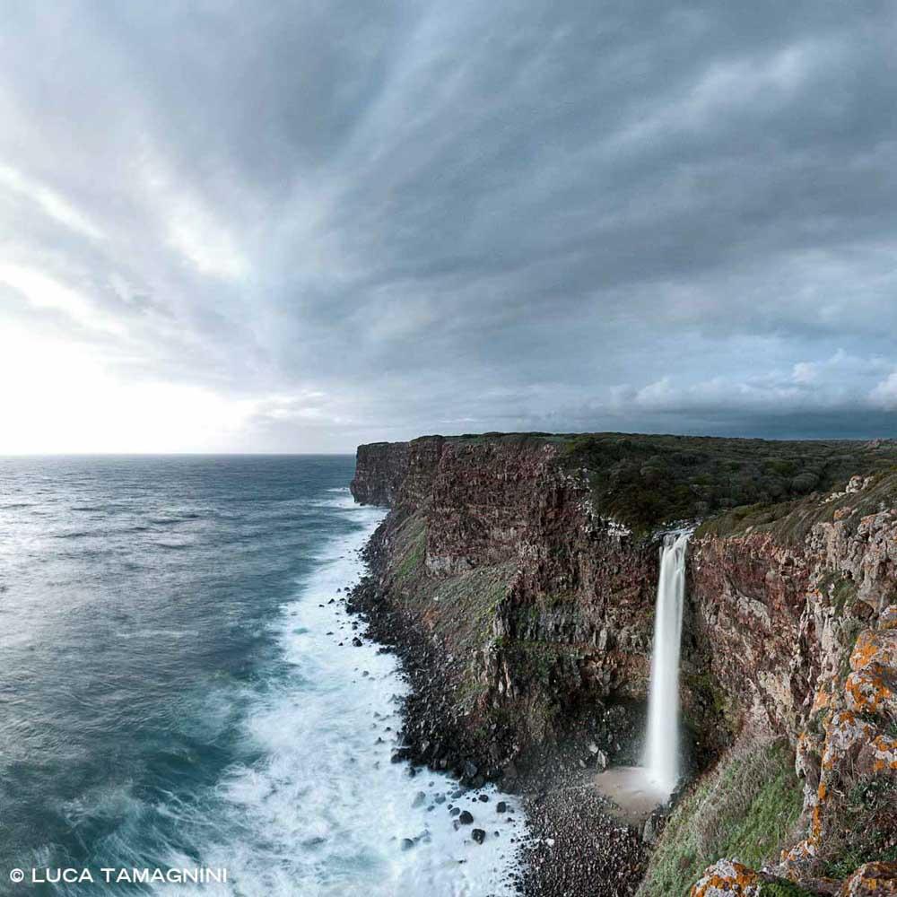 Cascata di Capo Nieddu. Saldo d'acqua in mare su costa basaltica mare mosso cielo nuvoloso.