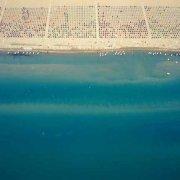 Lignano Sabbiadoro, la spiaggia ricoperta di ombrelloni e il mare rispreso dall'elicottero