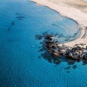 Villasimius, Spiaggia Timi Ama dal cielo con trasparenza dei bassi fondali marini e scogli di granito visti dall'alto