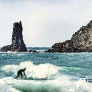 Un sufista tra il mare mosso sullo sfondo Punta di S'Enna 'e S'Arca