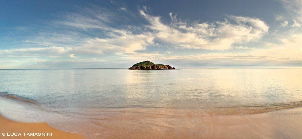 La Spiaggia di Su Giudeu (senza bagnanti) e l'Isola Su Giudeu nelle ultime luci del tramonto. Sullo sfondo un mare calmo